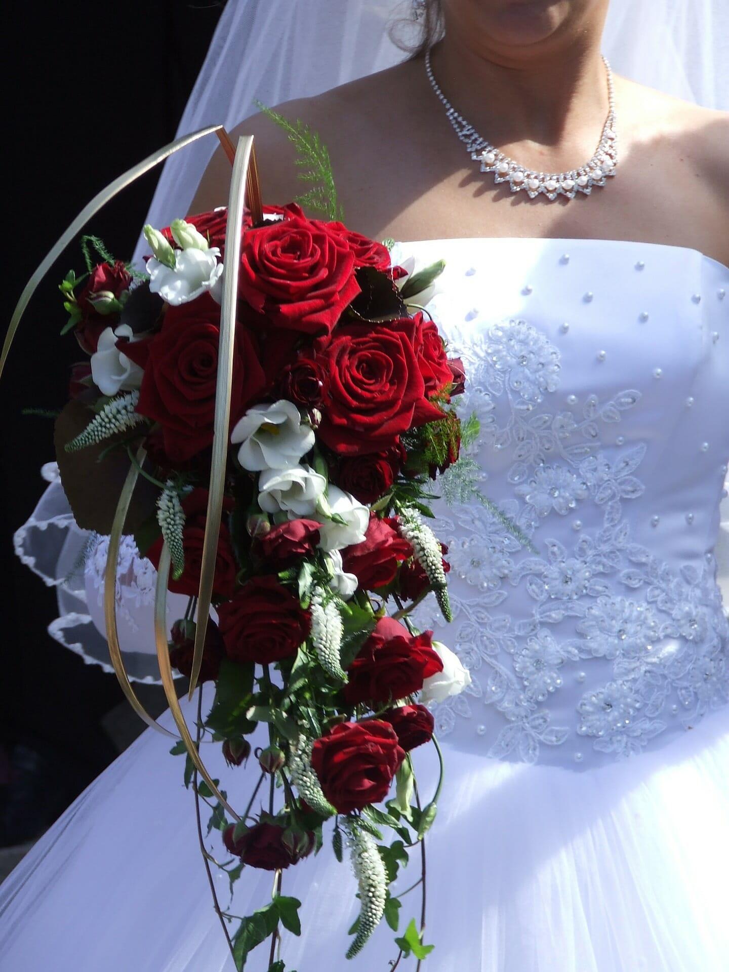 kobieta w białej sukni z bukietem czerwonych róż