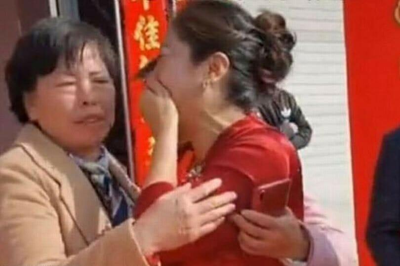 kobieta w beżowej marynarce obejmuje płaczącą kobietę w czerwonej sukience