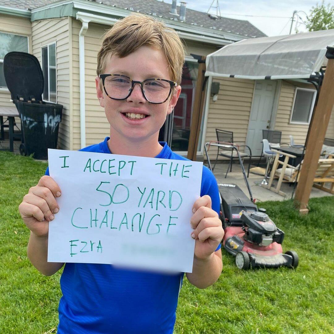 chłopiec trzyma w ręku kartkę z napisem