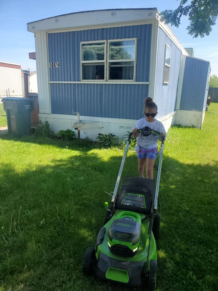 dziewczynka kosi trawę