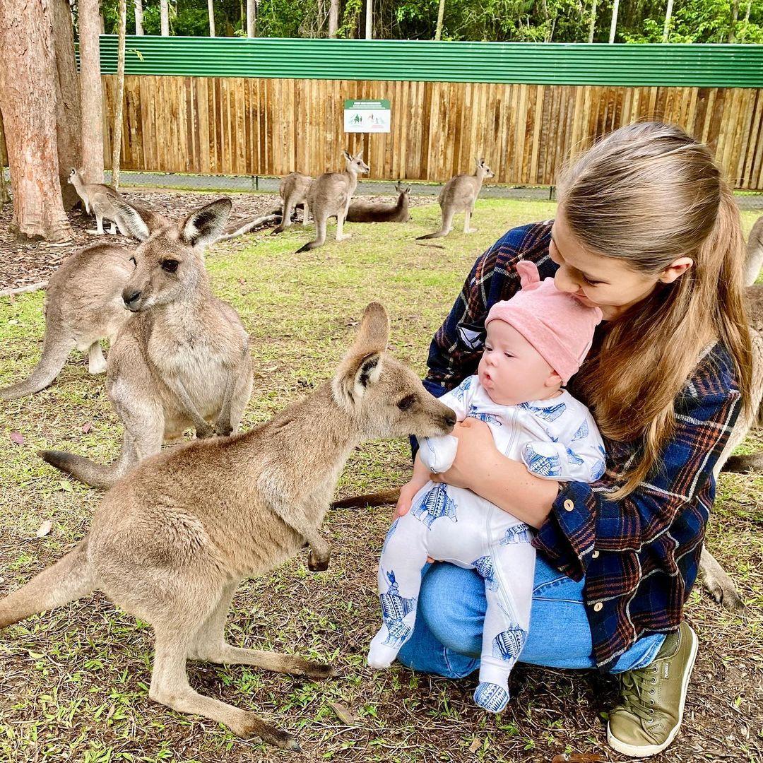 kobieta kuca z dzieckiem obok kangurzątka