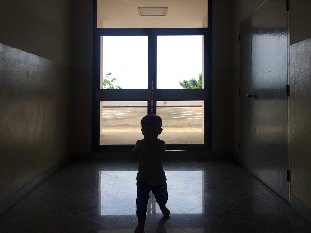 dziecko stoi na tle szklanych drzwi