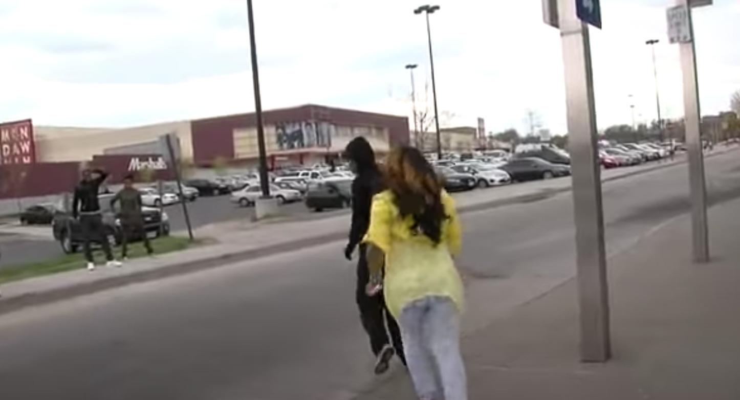 kobieta w żółtej bluzce i osoba w kapturze na ulicy