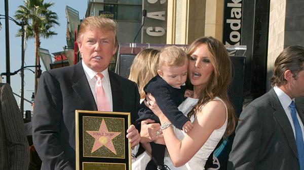 kobieta z dzieckiem na ręku i mężczyzna ze statuetką