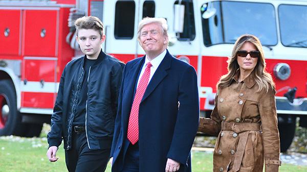kobieta w brązowym płaszczu, mężczyzna granatowym w garniturze i nastolatek w kurtce bomberce