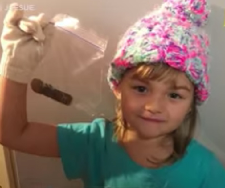 dziewczynka w różowej czapce na głowie trzyma  coś w woreczku srtrunowym
