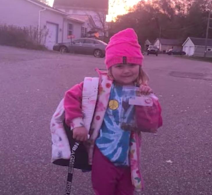 dziewczynka w różu z plecakiem na plecach trzyma w ręku woreczek