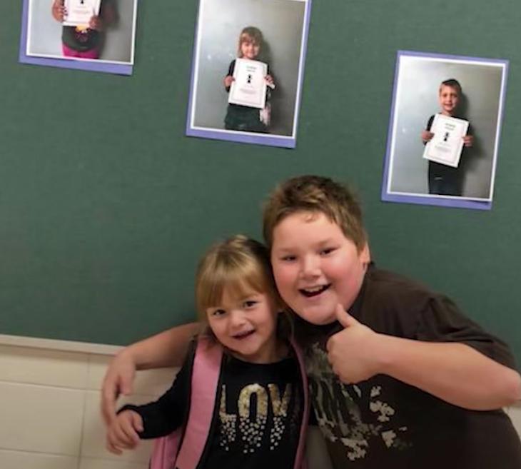 dziewczynka i chłopiec pozują na tle ściany ze zdjęciami