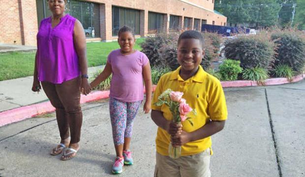 chłopiec w żółtej koszulce polo trzyma w ręku kwiaty, za nim stoi dziewczynka i kobieta
