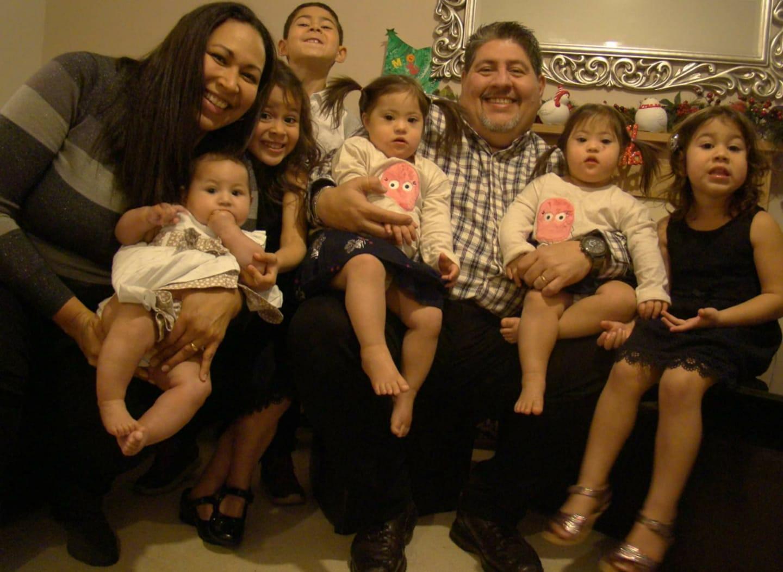 La foto della famiglia al completo, le gemelle con sindrome di down sono cresciute