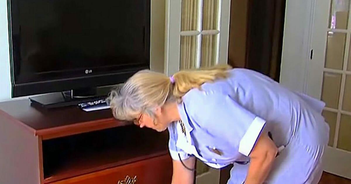 donna delle pulizie dell 39 hotel apre un cassetto nella camera di una coppia anziana guardate. Black Bedroom Furniture Sets. Home Design Ideas